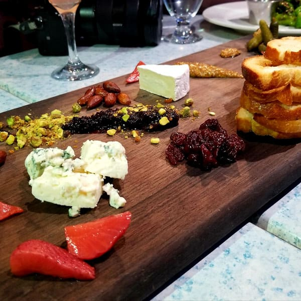 wooden snack platter from Belton chalet with cheese, bread, nuts, berries and jams