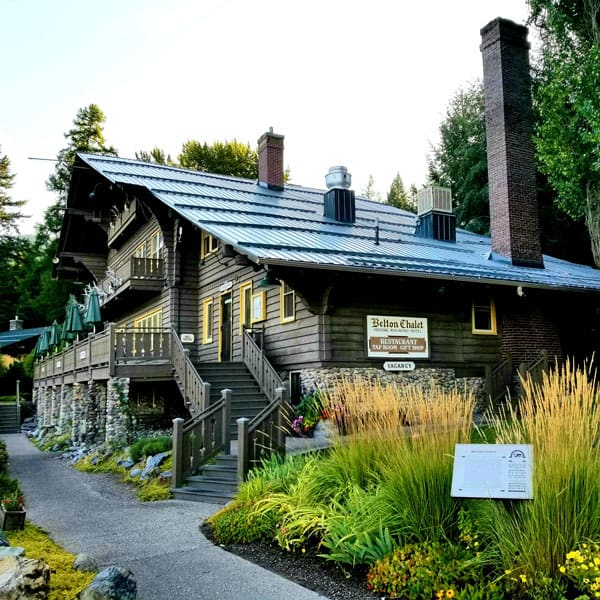 outside view of Belton Chalet Glacier National Park with wooden outside, deck and landscaping around it
