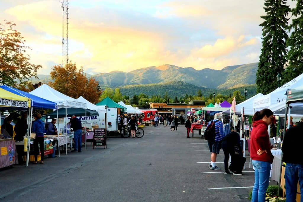 whitefish Montana Farmers market view of the market stands with people and a train engine and big mountain in the background