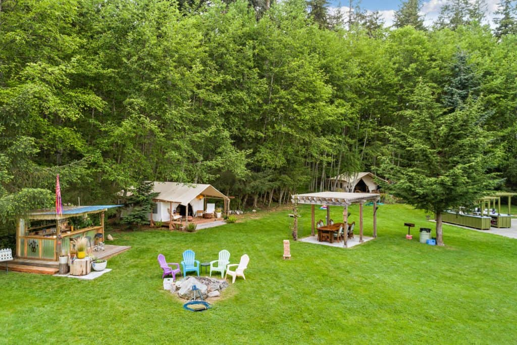 Grassy glamping site with tiki bar and outdoor kitchen