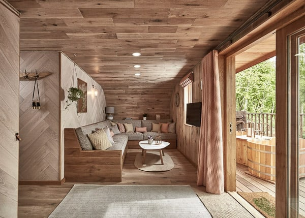 inside of a glamping cotswolds treeshouse with a view of a couch and wals, rug, sliding door to a deck with a tub