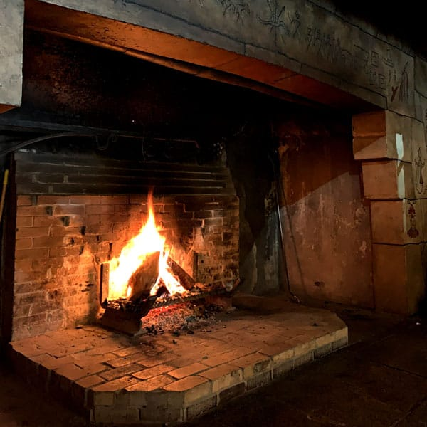 large brick fireplace with fire going