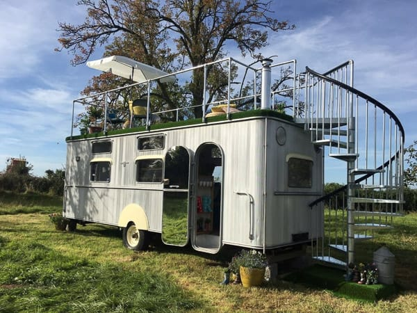 vintage glamping trailer with silver trim and deck on top