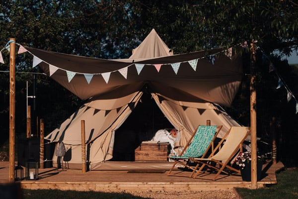 belle glamping tent with deck and chairs