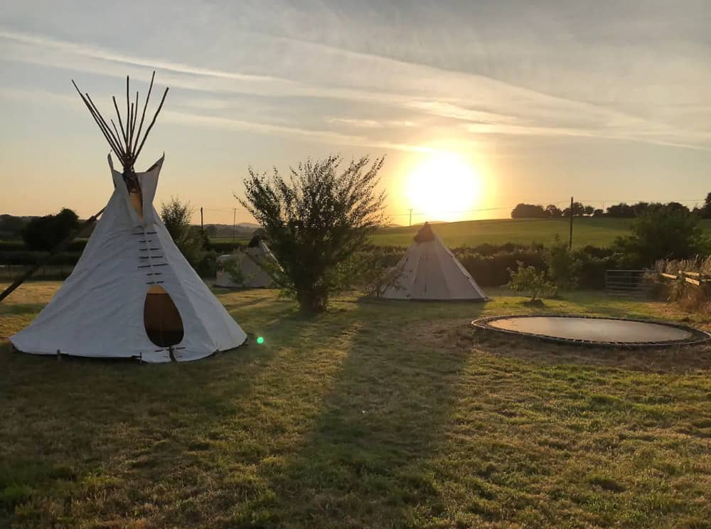 glamping tipis with sunset in the backgorund