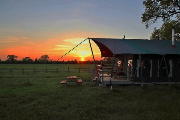 glamping tent with a sunset in the background