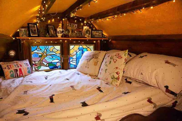 Gypsy Glamping Wagon view from inside of a bed and stained glass window