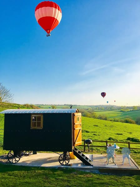Shephards hut in the Cotswolds view with ot air balloons in the sky