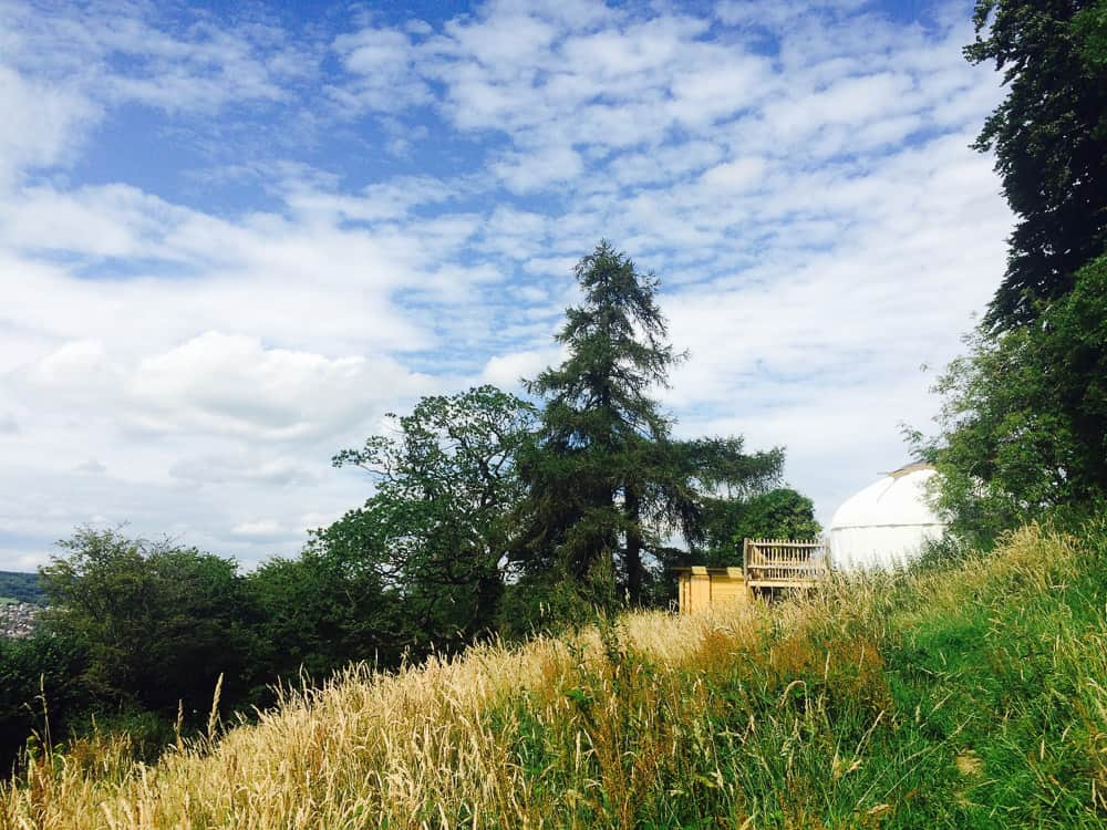 glamping yurt on a hill with trees and sky and clouds