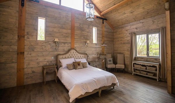 Glamping cabin inside view wit bed and high ceiling and window