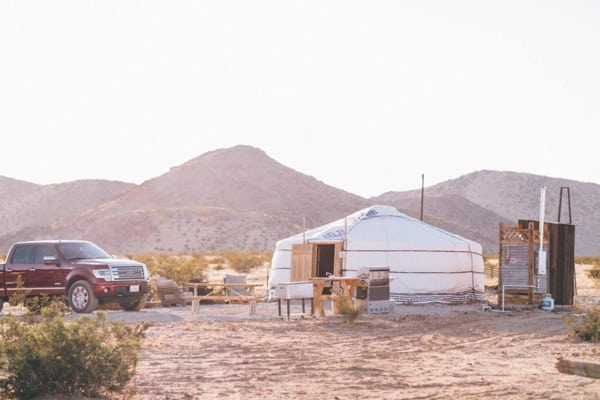 28 Palms Ranch Stargazing Yurt view of outside with shower and tables and truck