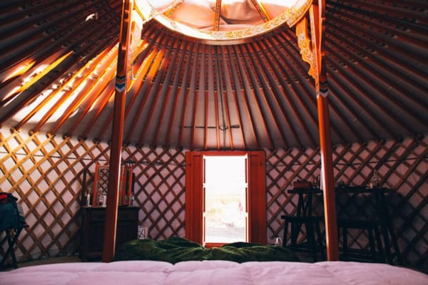 28 Palms Ranch Stargazing Yurt view of inside from bed with door and skylight