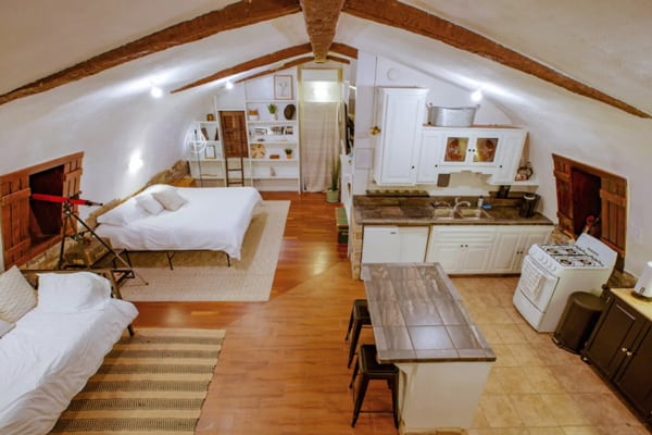 Moon Camp: an off-Grid Joshua Tree Glamping Retreat view of inside with bed, kitchen and couch