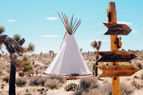 The Raising Sun Glamping Tipi at Lazy Sky view of tipi with sign in front in the desert