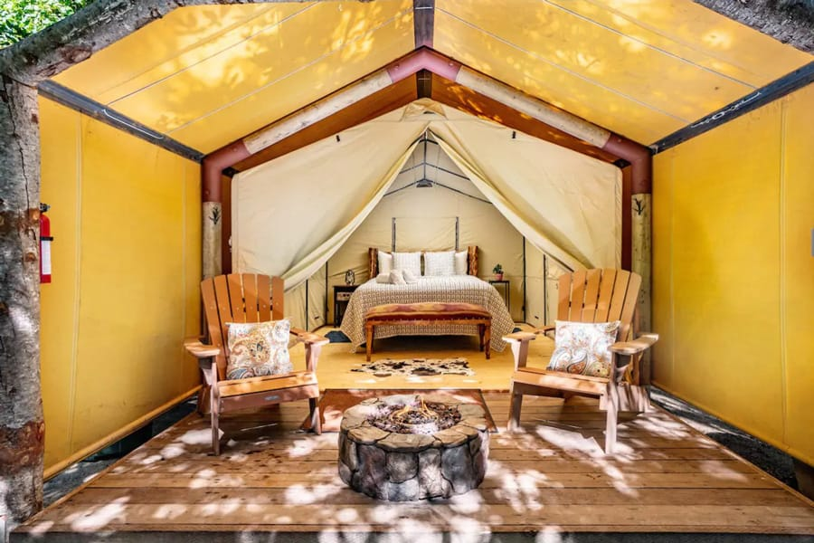Big Sur California Glamping Tent inside view with bed and chairs and fireplace