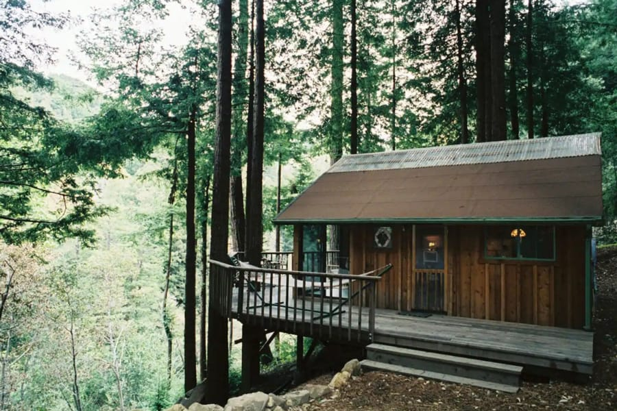 Big Sur Glamping Getaway - Rosehaven  view of cabin with deck looking out over valley with a forest