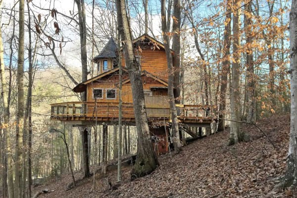 Asheville Glamping Treehouse of Luxury view from the side with wrap around deck on a hill