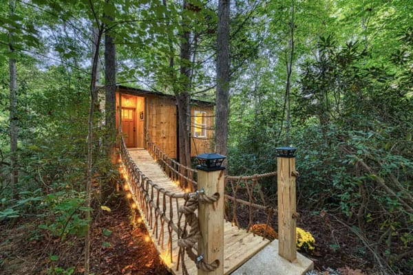 Romantic Asheville Treehouse with Hot Tub view from bridge with lights on and trees around it
