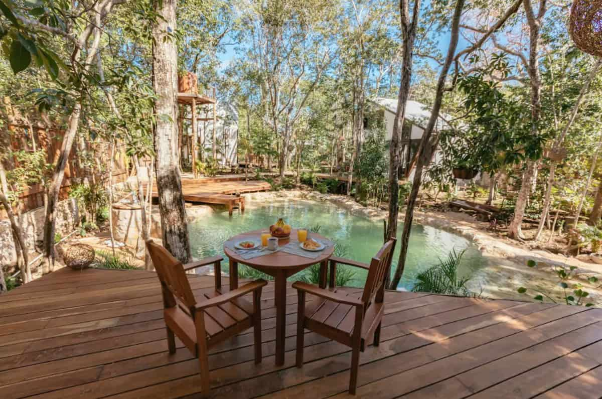 Chairs and table on a deck overlookign a cenote at Tulum glamping site