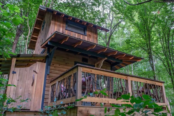 Peaceful Forest Treehouse Asheville NC view of the front of two story treehouse with deck among the trees