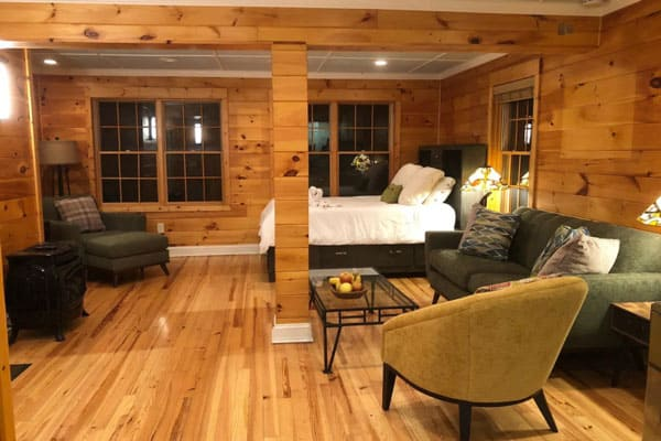 Happy Place Treehouse Black Mountain view of inside with bed, couch and chairs. Wooden walls