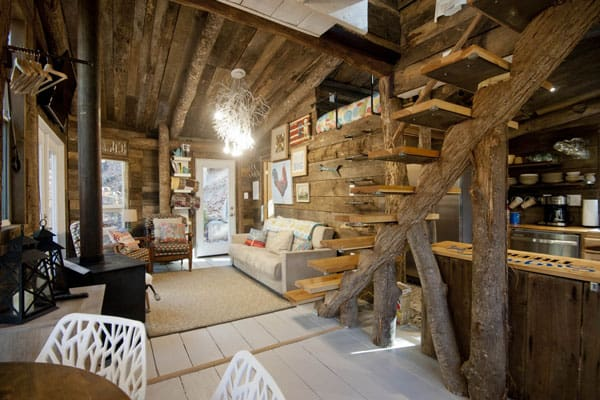 Sugar Creek Treehouse Asheville NC view from inside with couch, stove and staircase to loft