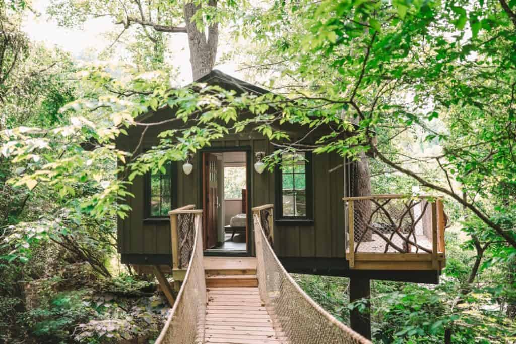 The Nest at Asheville Glamping view of the treehouse from bridge with door open and bed inside
