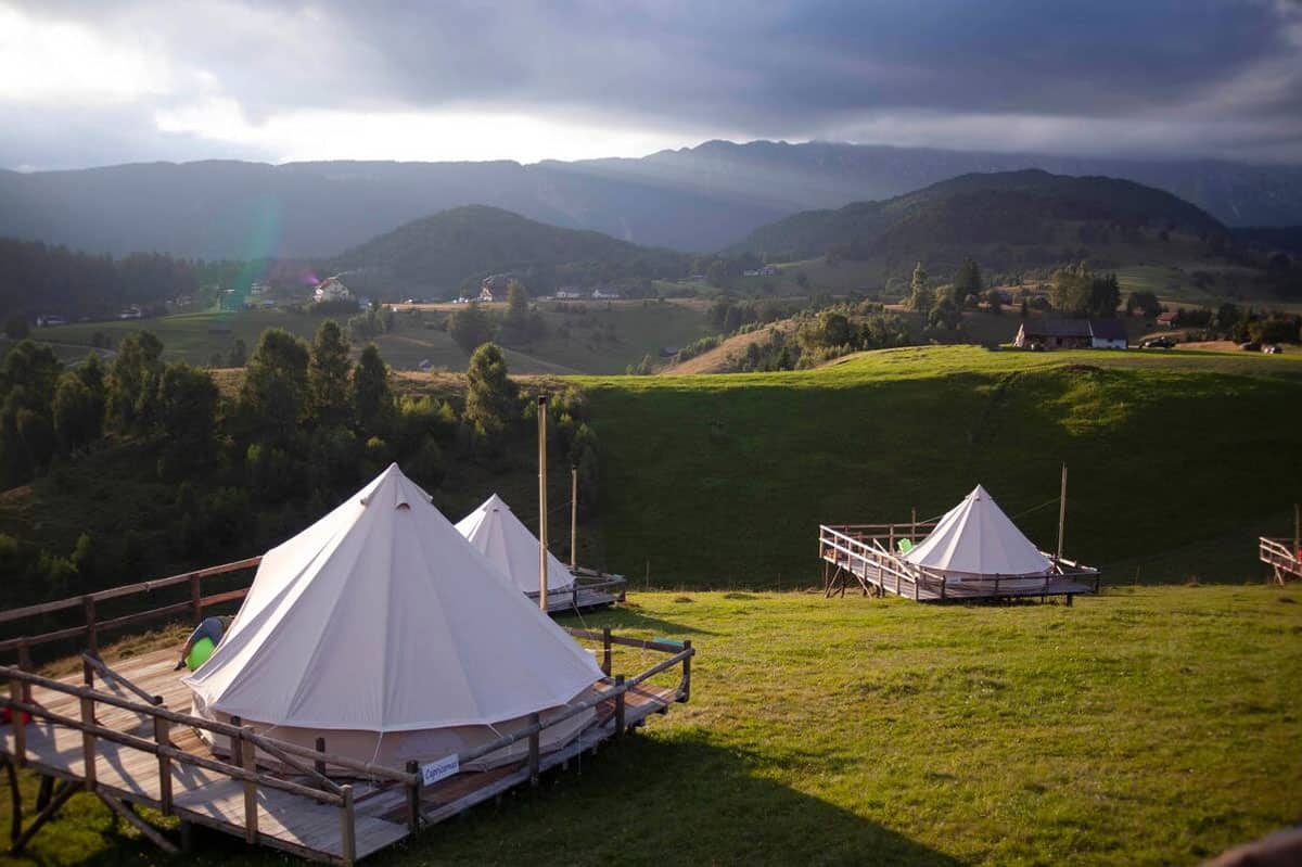 Best of Glamping Romania image of Ursa Mica Glamping Resort with view of the tents with the mountain range background