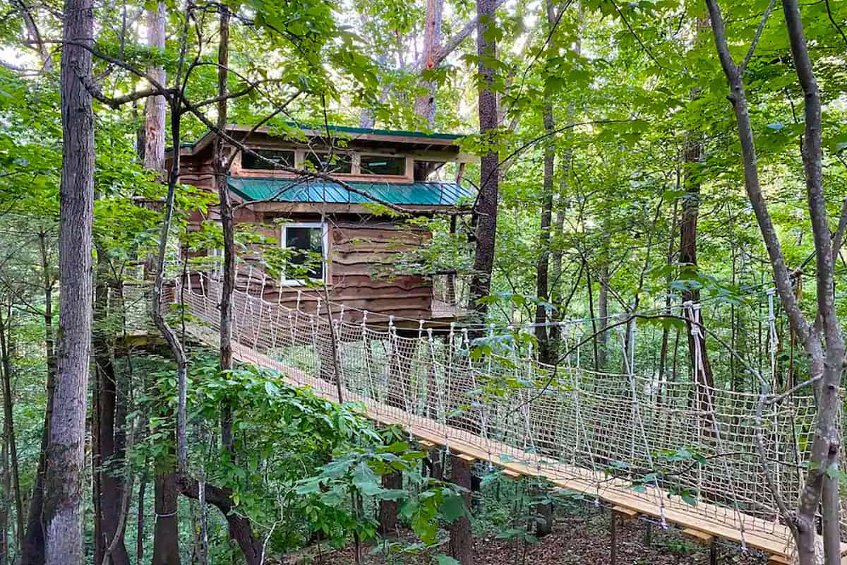 Asheville Treehouses in North Carolina featured image view of treehouse with hanging bridge to front door in the woods