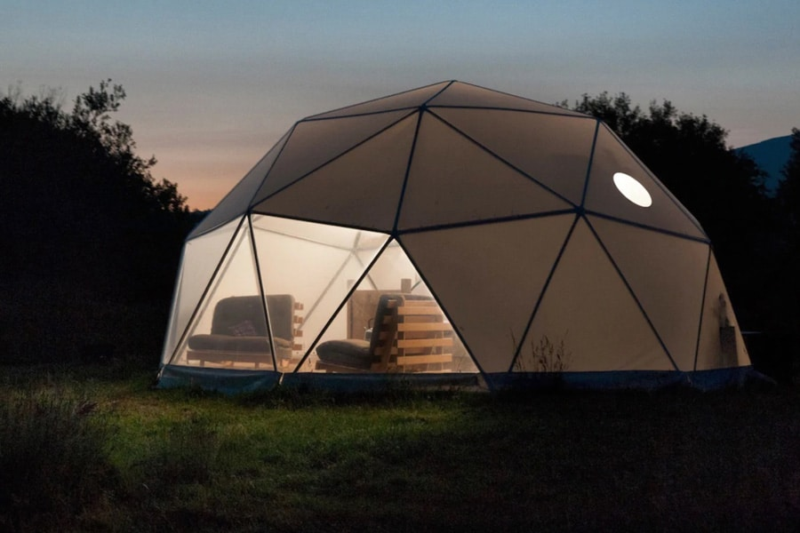 Dome Glamping North Wales view of geodesic dome at night with couches seen in the window
