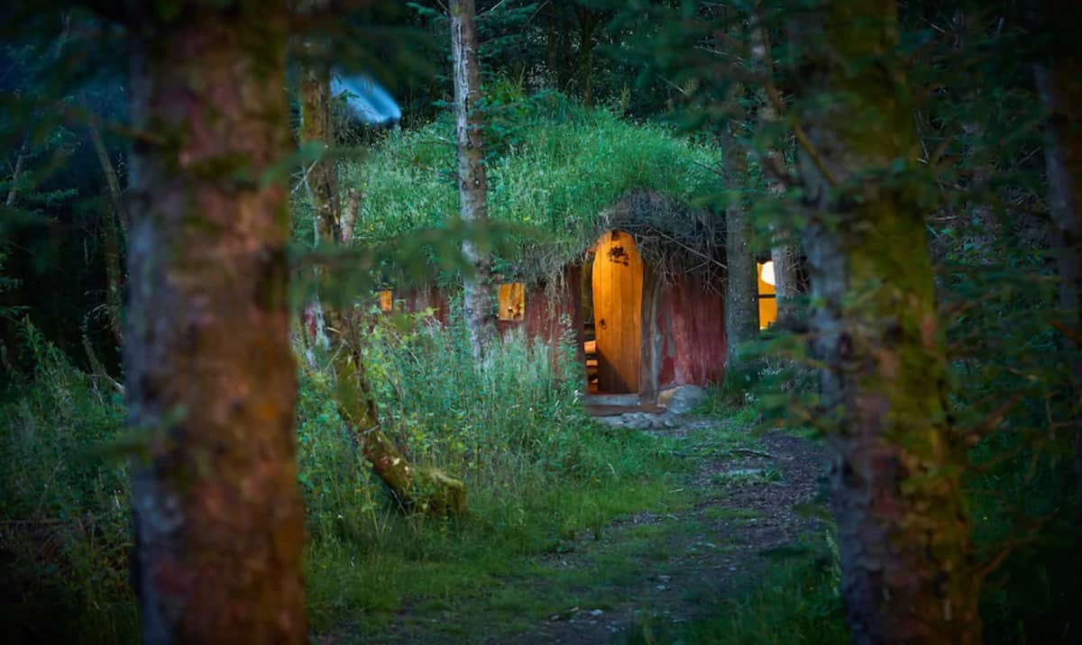 Magical Woodland Glamping North Wales Hobbit House view of the front through the trees and the lights on inside the earth house