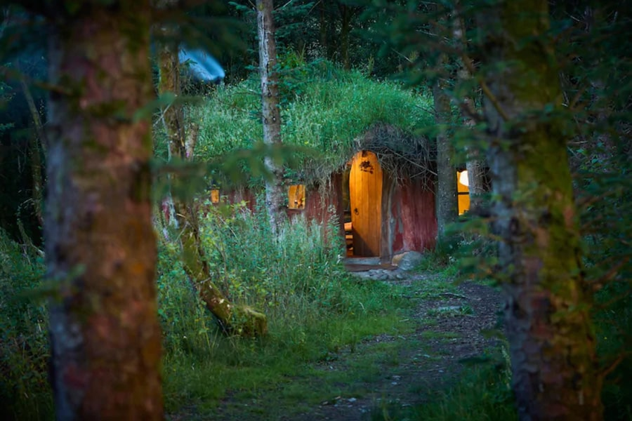 Magical Woodland Glamping Hobbit House view of the front through the trees and the lights on inside the earth house