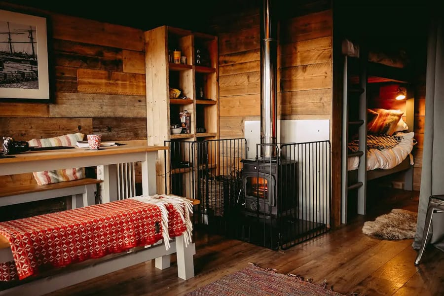 Llechwedd Glamping North Wales - Safari Tent view of inside of tent with bunk beds, stove and dining table