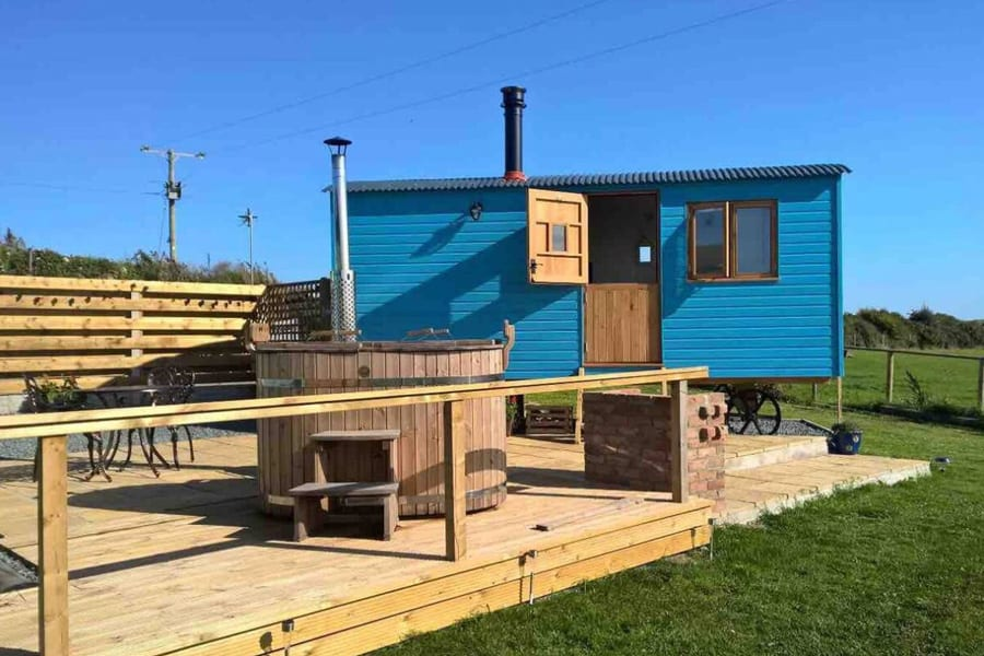 Isle of Anglesey Glamping with Hot Tub view of the blue shepherds hut with top half of door open and a deck with wooden hot tub on it