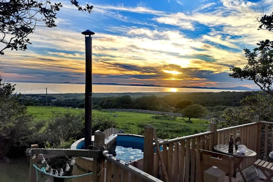 Shepherds Hut Glamping With Hot Tub North Wales view from the deck with hot tub and the sea in the distance at sunset