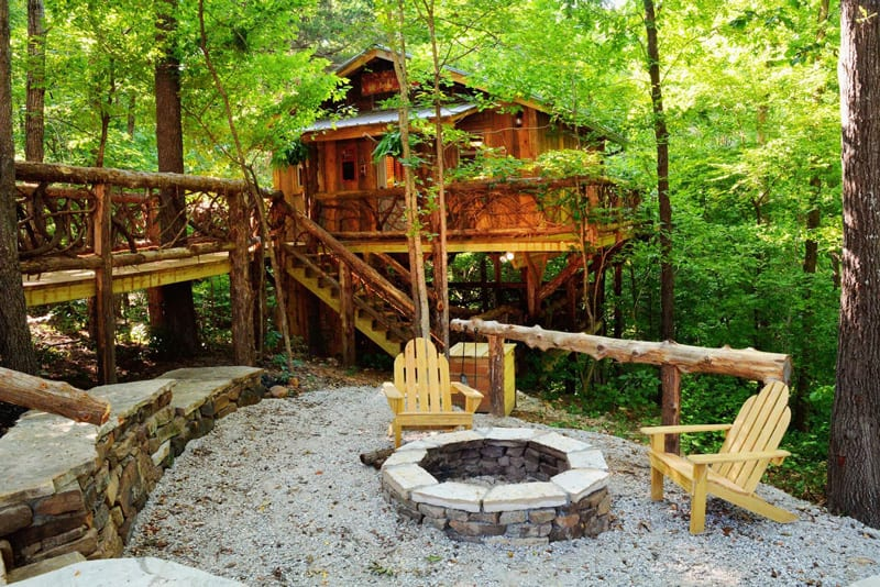 view of treehouse glamping Arkansas with firepit and bridge to wooden treehouse in the forest