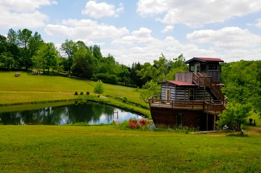 Tennessee Glamping at The Ark  view of the Ark looking cabin next to a pond and green trees and grass