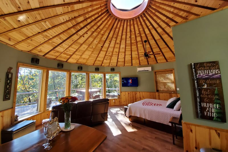 view of inside of Eureka yurts in Arkansas with bed, couch and table