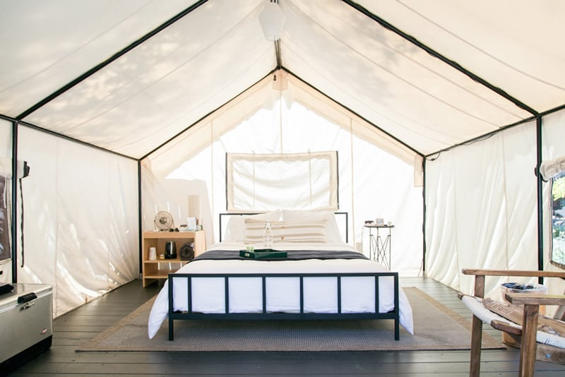 autocamp luxury glamping tent view of inside with bed, chair, nightstand and canvas walls