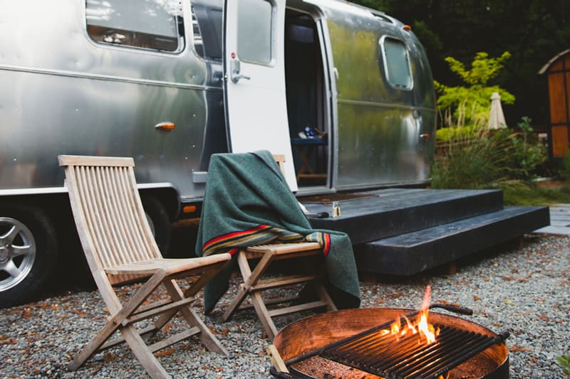 glamping airstream bay area autocamp view of the firepit, to wooden chairs and the side of the airstream