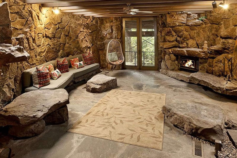 view of basement of glamping cottage Arkansas with stone walls and furniture, couch and fireplace