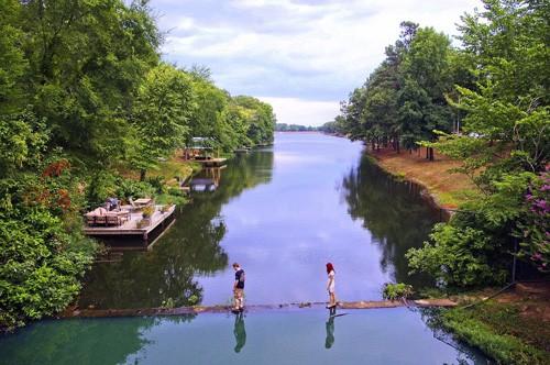 view of 2 people walking across foot bridge on lake number two in Arkansas