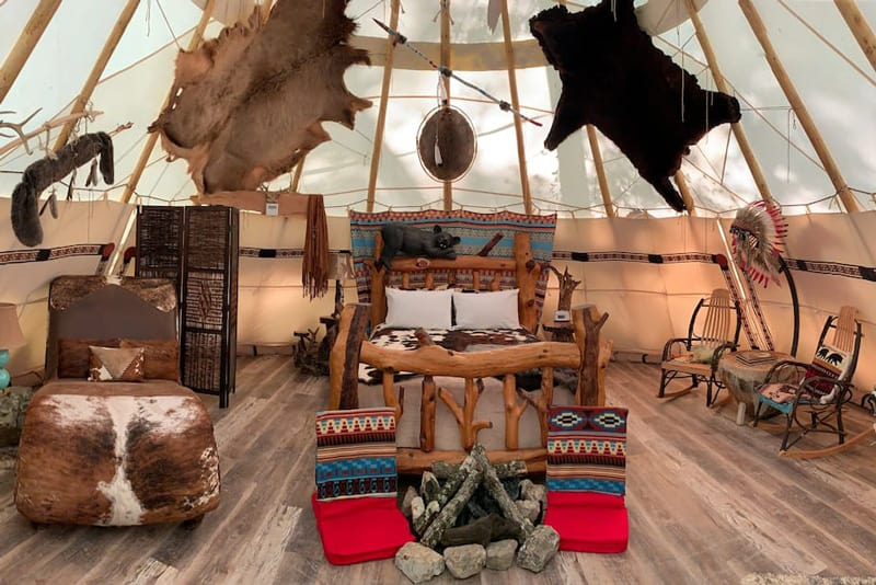 Lakota Luxury Tipi Arkansas Glamping view of inside of tipi with native decorations and log bed and animal skins on furniture