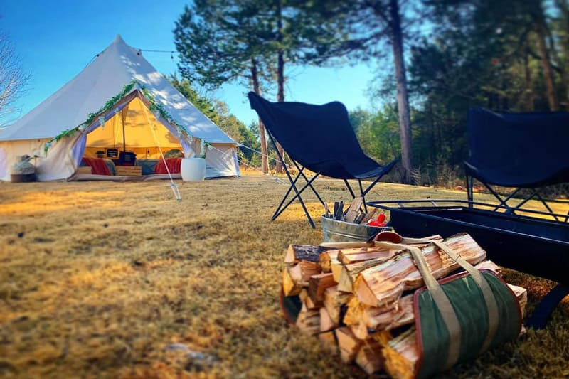 Luxury Bell Tent Glamping in the Ozarks view from firepit with stack of wood and bell tent in the background