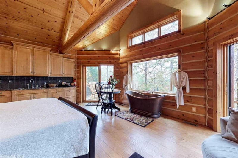 inside view of log cabin Arkansas with bed, tub, kitchen and windows