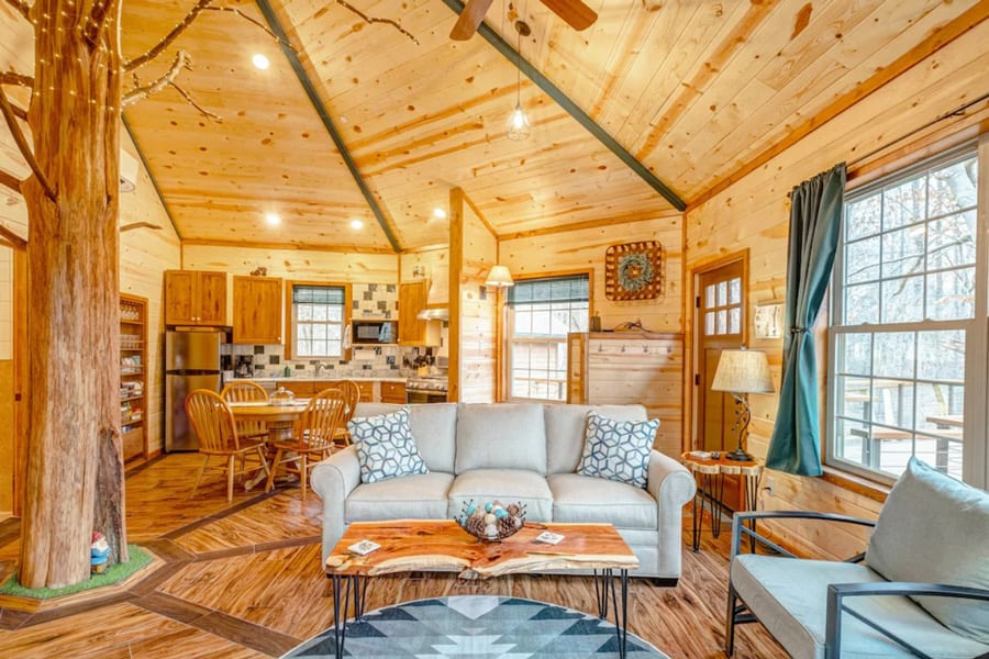 Luxury Treehouse -  Glamping Nashville Area Getaway view of inside. All wood with tree growing through room, windows, couch and kitchen