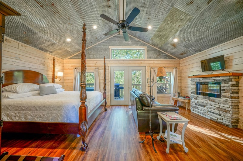 Mountain Air Treehouse Glamping in Arkansas view of inside with poster bed, couch, wood floors and deck outside