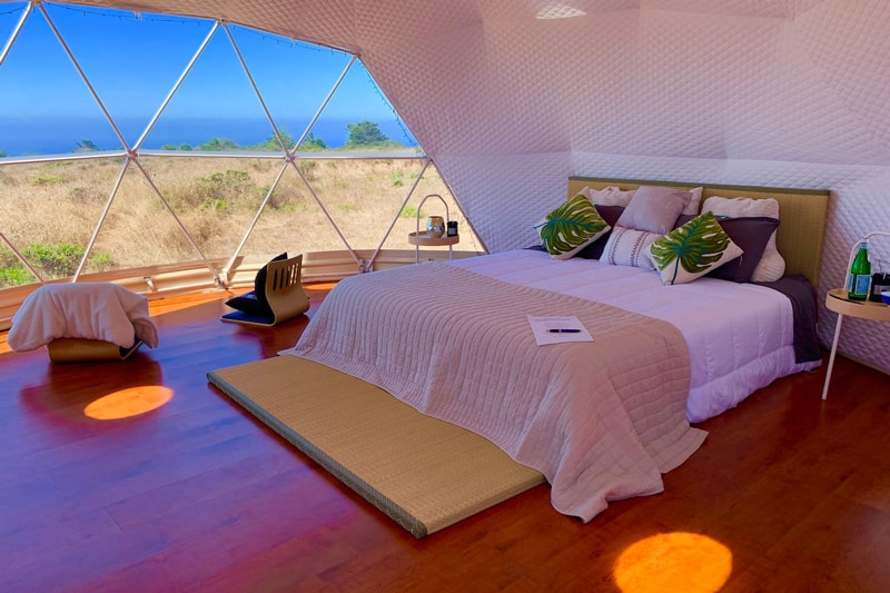 glamping dome bay area view from inside with bed and chairs and large windows with a view