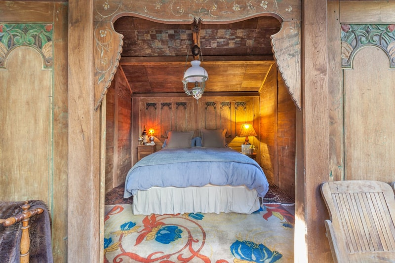 swallowtail glamping hut view of the bedroom with wood carvings and decorations