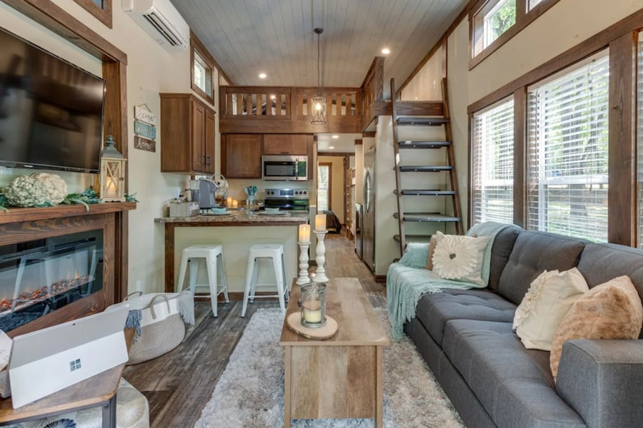 Serenity by The Falls tiny home view of the inside with couch, kitchen, fireplace and loft